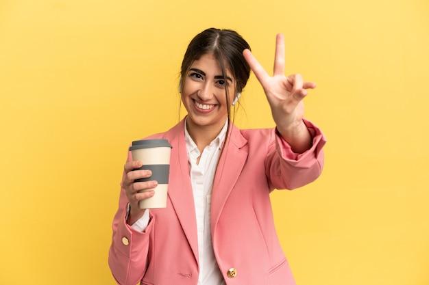Donna caucasica di affari isolata su fondo giallo che sorride e che mostra il segno di vittoria