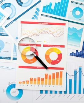 Grafico aziendale e lente d'ingrandimento sul desktop. il concetto di analisi e determinazione delle informazioni chiave nel mondo degli affari.