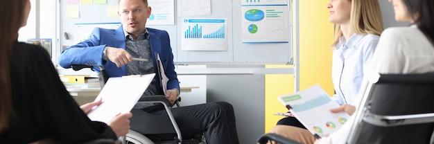 Business coach in sedia a rotelle conduce riunioni di lavoro dei dipendenti. concetto di sviluppo di avvio