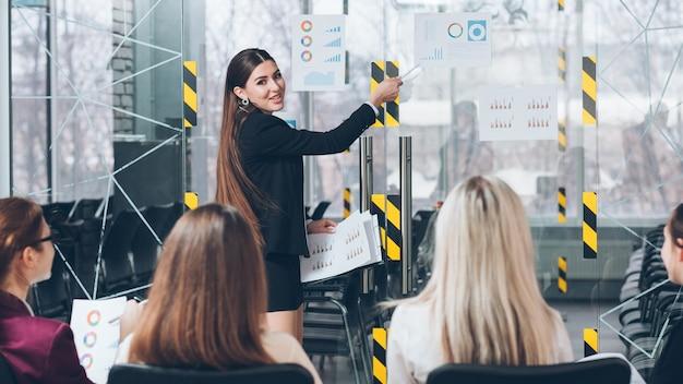 Formazione aziendale. formazione aziendale avanzata. allenatore sorridente che indica i tassi di crescita previsti.