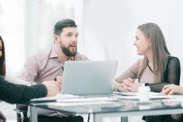 I colleghi di lavoro discutono di dati finanziari seduti alla scrivania