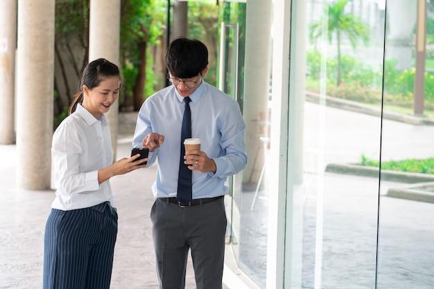 Colleghi di lavoro che discutono di problemi di lavoro all'aperto vicino all'edificio per uffici, parlando tra loro all'aperto.
