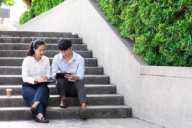 Colleghi di lavoro che discutono di problemi di lavoro all'aperto vicino all'edificio degli uffici, parlando tra loro all'aperto.
