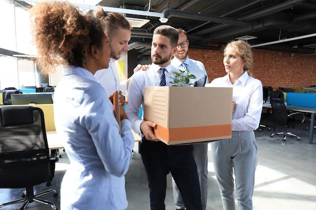I colleghi di lavoro salutano il dipendente licenziato.