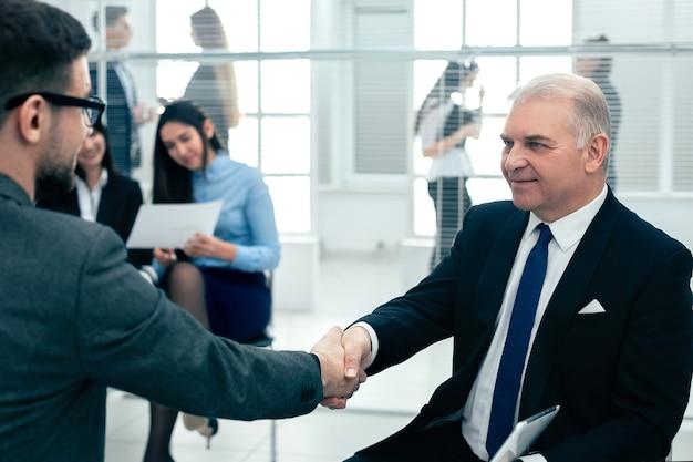 I colleghi di lavoro si stringono la mano seduti nella sala conferenze