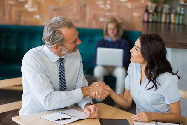 Colleghi di lavoro si stringono la mano dopo una riunione di successo