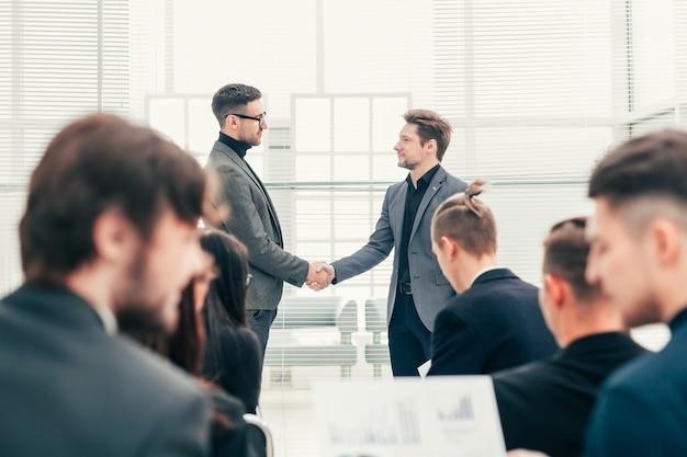 Colleghi di lavoro si stringono la mano durante una riunione. il concetto di successo