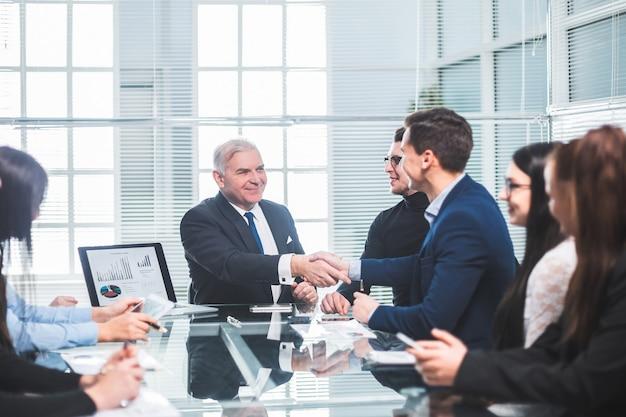 Colleghi di lavoro si stringono la mano durante una riunione di lavoro. il concetto di lavoro di squadra