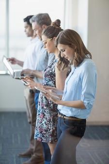 Colleghi di lavoro in fila utilizzando il telefono cellulare, tablet digitale e laptop