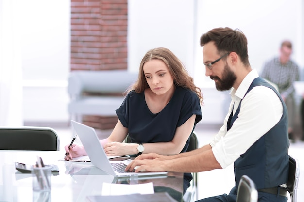 Colleghi di lavoro che utilizzano un computer portatile sul posto di lavoro
