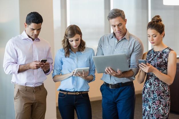 Colleghi di lavoro che utilizzano telefono cellulare, tablet digitale e laptop