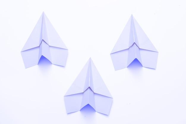 Concorrenza aziendale. tre aeroplani di carta blu cielo isolati su bianco