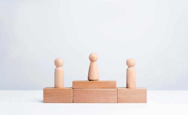 Vincitore del concorso aziendale. donne in piedi sul podio del vincitore del primo premio, figura in legno su blocco cubo di legno su sfondo bianco con spazio per le copie. obiettivi, successo e concetto di leadership.