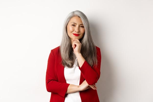 Concetto di affari. donna d'affari asiatica matura che sorride compiaciuta, sembra premurosa, ha un'idea, in piedi in blazer rosso su sfondo bianco