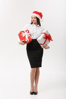 Concetto di affari bella giovane donna caucasica di affari con il cappello della santa che tiene i contenitori di regalo con lo spazio della copia dal lato