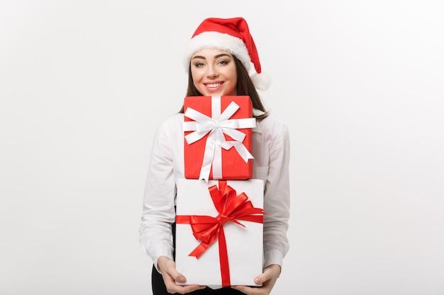 Concetto di affari bella giovane donna caucasica di affari con il cappello della santa che tiene molti contenitori di regalo con lo spazio della copia dal lato