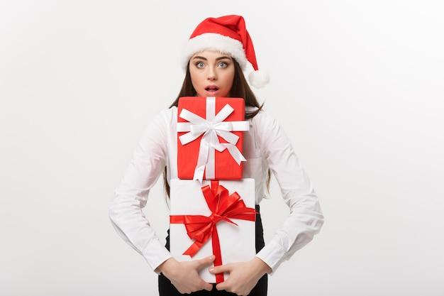 Concetto di affari bella giovane donna caucasica di affari con il cappello della santa che tiene molti contenitori di regalo con l'espressione facciale sorprendente