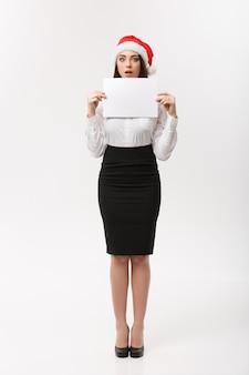 Concetto di affari - bella giovane donna sicura di affari con il cappello della santa che tiene carta in bianco bianca con l'espressione facciale sorprendente.