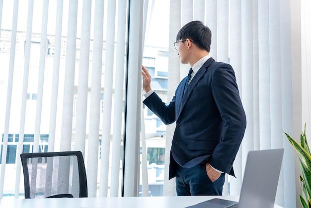 Il concetto di business l'amministratore delegato che separa il sipario guardando fuori dal vetro trasparente dall'ufficio.