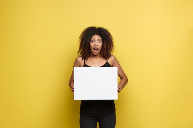 Concetto di business - close up ritratto di giovane bella attraente afroamericano che punta il dito al semplice bianco segno bianco. giallo pastello studio sfondo. copia spazio.