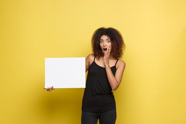 Concetto di business - close up ritratto di giovane bella attraente afroamericano sorridente mostrando segno bianco vuoto bianco. giallo pastello studio sfondo. copia spazio.