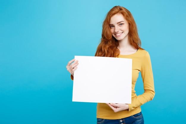 Fine di concetto di affari sul ritratto giovane bella ragazza attraente dei capelli rossi dello zenzero che sorride mostrando lo spazio pastello blu della copia della parete del segno in bianco