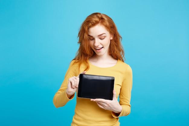 Concetto di affari close up ritratto giovane bella ragazza attraente redhair sorridente che mostra lo schermo digitale della compressa sulla parete pastello blu nera