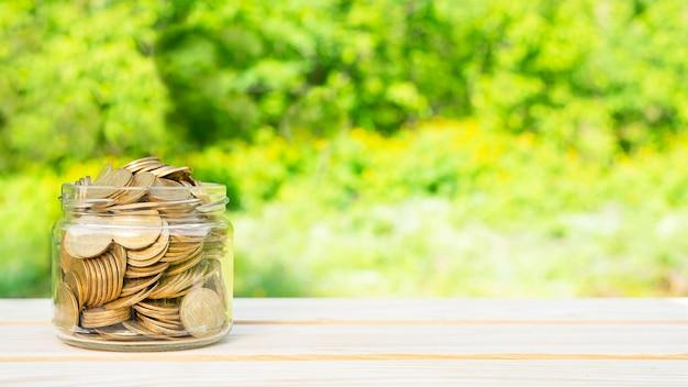 Concetto di affari. monete in un barattolo su un tavolo di legno.