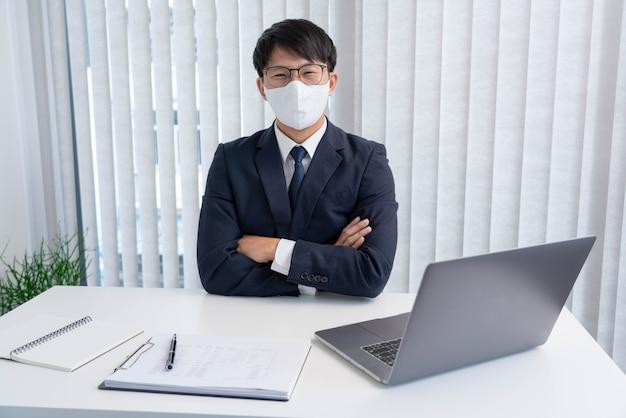 Concetto di affari il dirigente maschio fiducioso che indossa l'abito seduto alla scrivania con il laptop e i documenti sulla parte superiore.