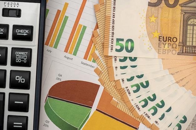 Banconote in euro di concetto di affari con penna e calcolatrice grafici. finanza