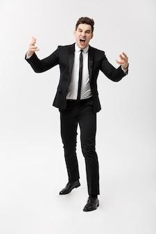 Concetto di affari: ritratto a figura intera di un uomo d'affari pazzo in tuta che urla e urla mentre si trova su uno sfondo grigio isolato.