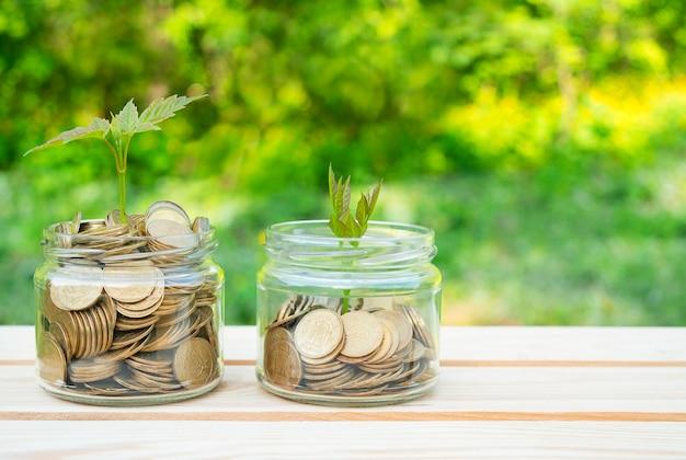 Concetto di affari. barattoli di vetro pieni di monete stanno su un tavolo di legno. bilancio familiare, accumulo di denaro. copia spazio.
