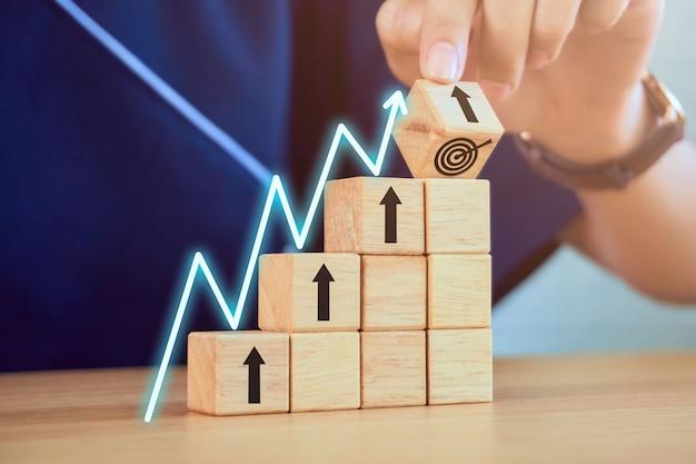 Successo obiettivo del concetto di business. primo piano della mano che tiene l'impilamento dei blocchi di legno e grafico di crescita sulla tavola.