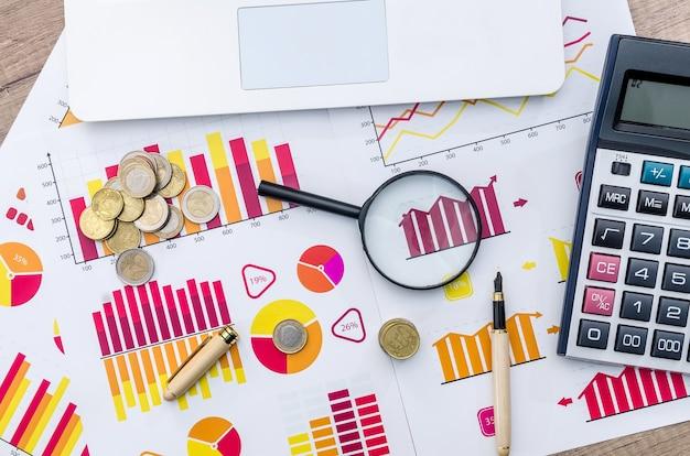 Concetto di affari - grafico, lente d'ingrandimento e calcolatrice