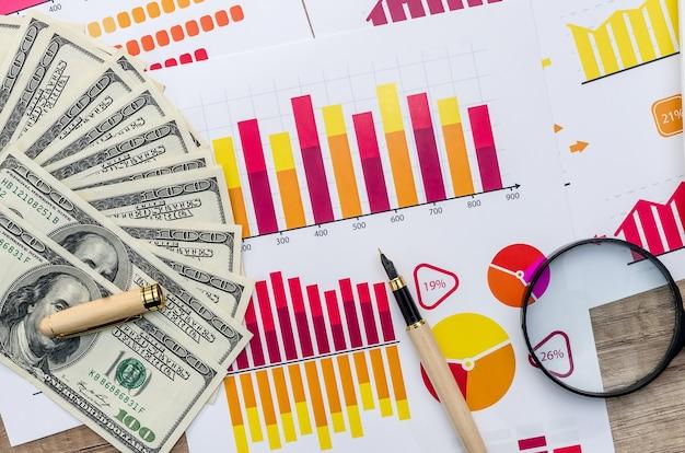 Concetto di affari - grafico, lente d'ingrandimento e dollaro