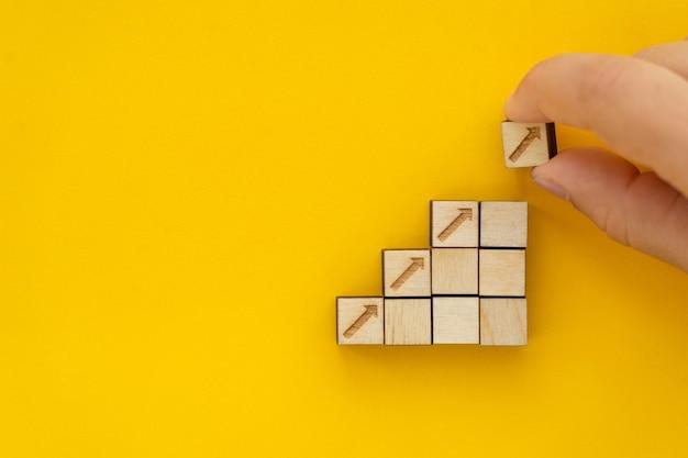 Processo di successo della crescita del concetto di business primo piano mano della donna che dispone l'impilamento di blocchi di legno come passaggio