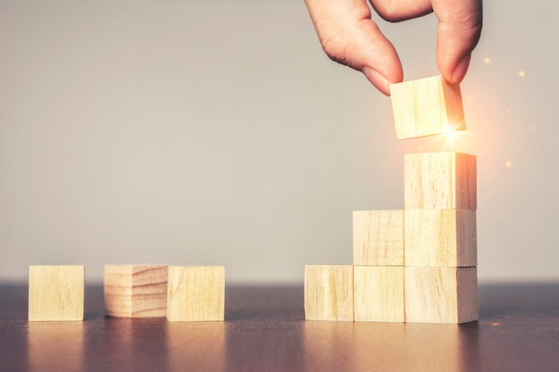 Processo di successo di crescita del concetto di affari e mano che organizza l'impilamento del blocco di legno come scala di gradino sul tavolo.