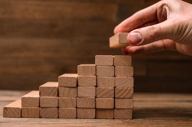 Concetto di affari - la mano costruisce una scala da blocchi di legno. guidare il business al massimo del concetto.