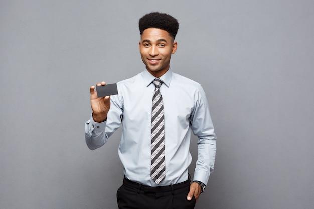 Concetto di affari - uomo d'affari afroamericano professionista bello felice che mostra la carta di nome al cliente.