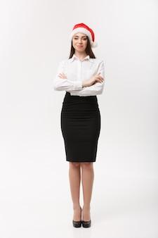 La donna caucasica moderna di affari di concetto di affari nel braccio di tema di natale ha attraversato la posa sulla parete bianca con lo spazio della copia
