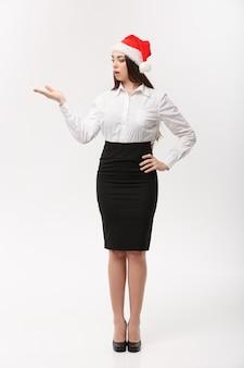 Business concetto moderno caucasico donna d'affari nel muro bianco tenendo la mano sul lato presentando il prodotto