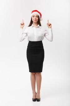 Business concetto moderno caucasico donna d'affari nel muro bianco che punta il dito verso l'alto presentando il prodotto