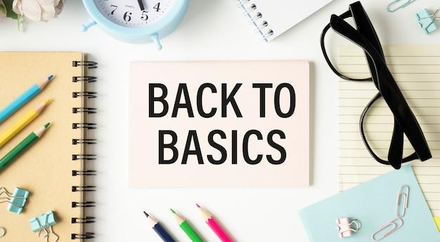 Concetto di affari. notebook con testo back to basic foglio di carta bianca per appunti su sfondo bianco