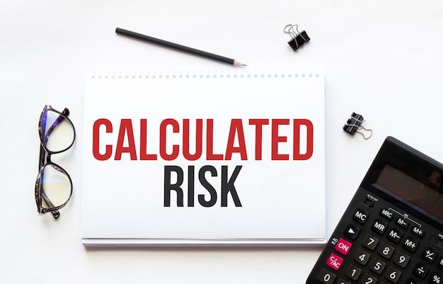 Concetto di affari. notebook con testo foglio di carta bianca del rischio calcolato per appunti, calcolatrice, occhiali, matita, penna