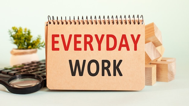 Concetto di affari. notebook con testo foglio di lavoro quotidiano di carta bianca per note, calcolatrice, blocchi di legno, lente d'ingrandimento, sullo sfondo