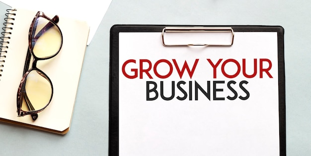Concetto di affari notebook con testo grow your business foglio di carta bianca per bicchieri di note sullo sfondo bianco