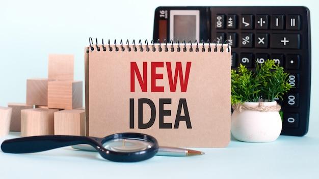 Concetto di affari. notebook con testo nuova idea foglio di carta bianca per note, calcolatrice, lente d'ingrandimento, blocchi di legno, sullo sfondo dei grafici.