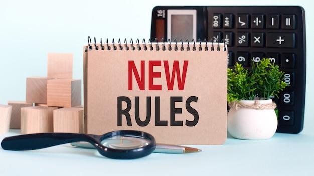 Concetto di affari. notebook con testo nuove regole foglio di carta bianca per note, calcolatrice, lente d'ingrandimento, blocchi di legno, sullo sfondo dei grafici.