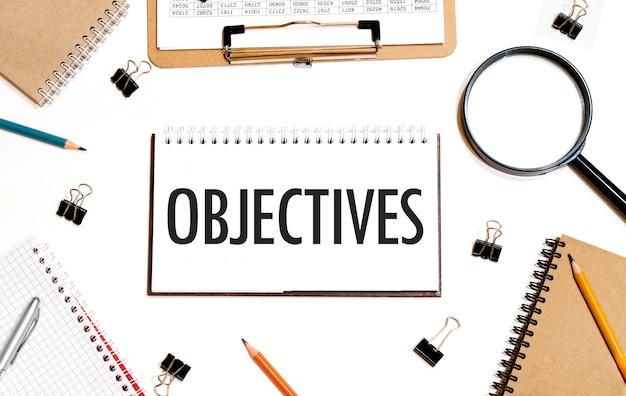 Concetto di affari. notebook con testo project manager foglio di carta bianca per appunti, calcolatrice, bicchieri, matita, penna, in fondo bianco