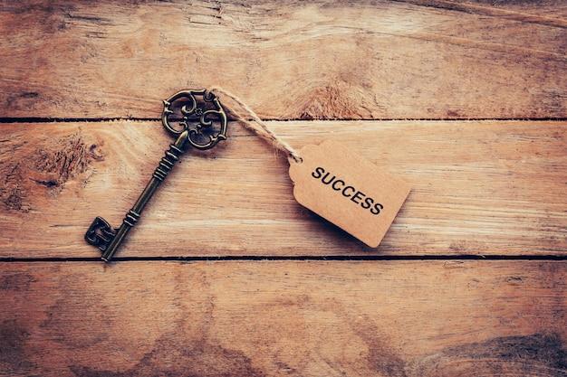Concetto di affari - vecchia annata chiave su legno con il tag successo.